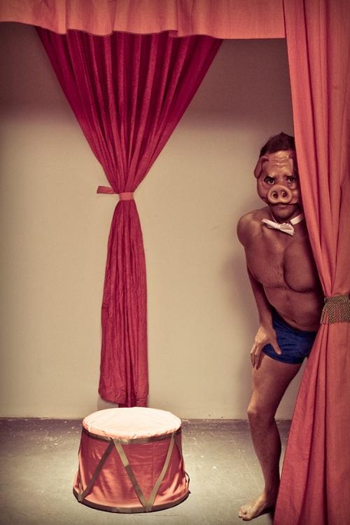 photography of AJ Valadka man wearing a pig nose behind a curtain