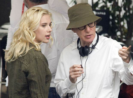 Woody Allen wearing a hat as he directs Scarlett Johansson