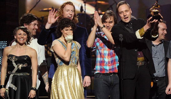 Win Butler of Arcade Fire hoisting a Grammy for album of the year 2011