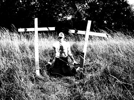 A man kneeling between two crosses in the film burning inside