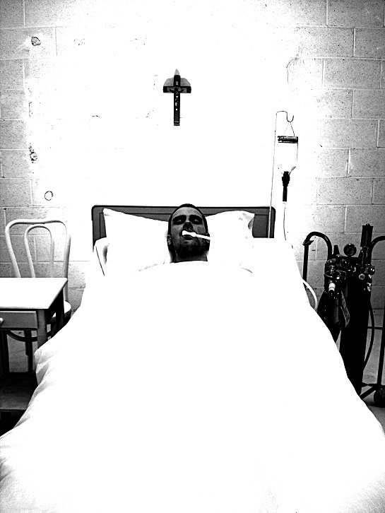 man sick in a bed below a cross in a film called burning inside