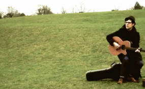 Stylusboy playing guitar with a suitcase in the UK in his video for Whole Picture