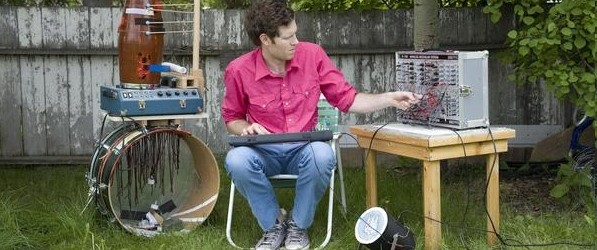 Chad Vangaalen playing a bunch of instruments in a yard