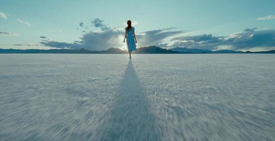 A Woman walking toward the sun and sky
