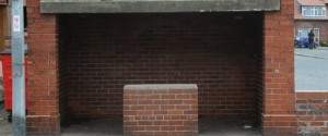 Photo of brick three walled bus stop shelter