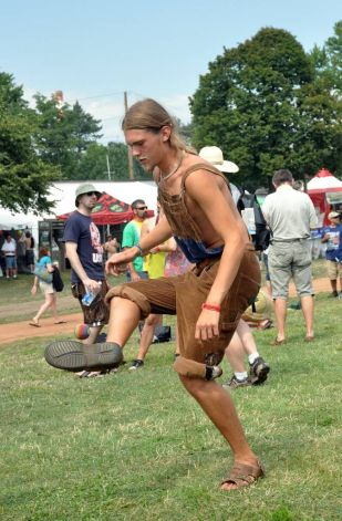 Young blonde dude with a beard playing HackySack at a festival