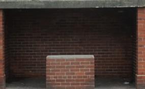Photo of empty desolate brick bus shelter stop
