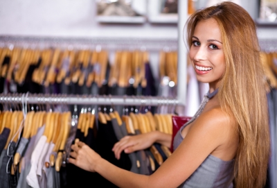 a blonde woman in a shop with a large smile