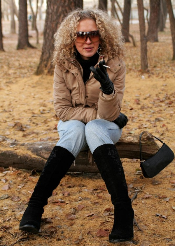 nostalgic woman smoking in the park and wearing large sunglasses